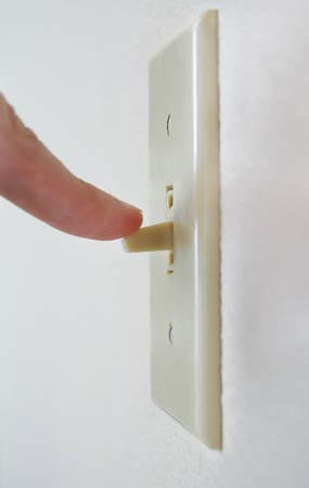 A single light switch on a white wall at an angle with a finger flipping it down, to turn it off and save power.