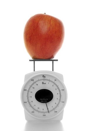 Red apple sitting on a miniature scale isolated on white background photo