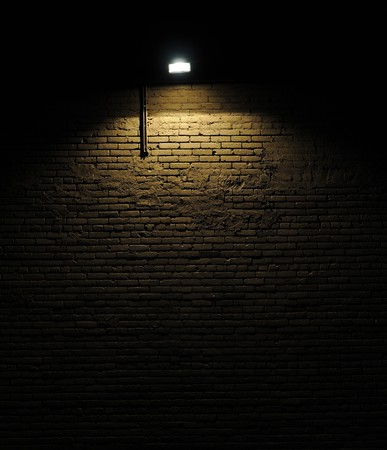 brick wall background: Old rough brick wall background texture with a spotlight shining on it Stock Photo