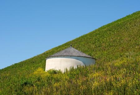 cisterna: Una torre de agua de la cisterna en medio de un campo en una colina.