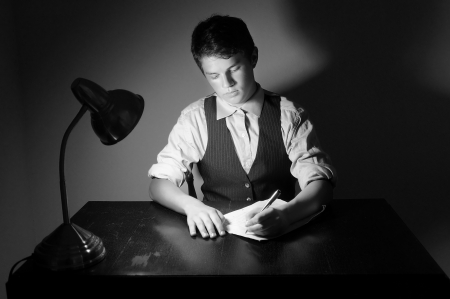 A young adult man writing a letter on a desk with a lamp.  photo