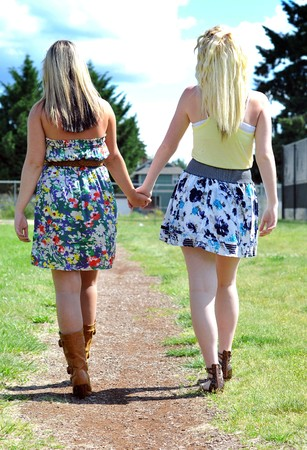 Two beautiful young blond ladies in a dress and skirt walk down a dirt pathway on a bright summer's day while holding hands. Stock Photo - 7680131