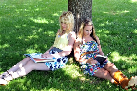 Young white Caucasian teenage girl friends sit under a tree in the shade reading a book and doing homework. photo