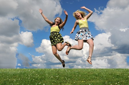 Two young girls jumping over a grass hill with their arms up in the air below the blue sky with white clouds. Stock Photo