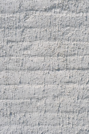 A white roughly textured brick wall painted with white paint photo