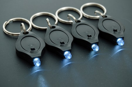 Miniature LED keychain lights on a black surface with shallow depth of field.