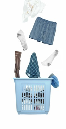 A bunch of dirty laundry clothes fly out of the laundry basket. Cutout isolated on white background.