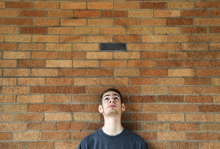 above head: Young caucasian male looks up above his head leaning against a brick wall.