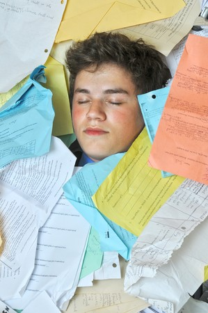 sleep: Young male student is overwhelmed by way too many homework assignments.