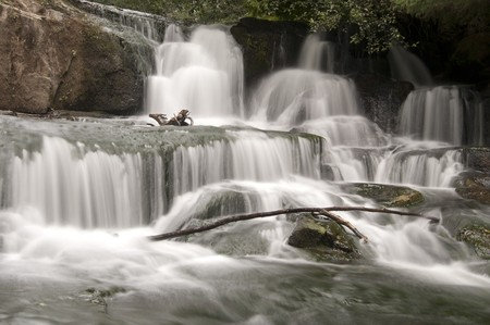 Long exposure of a waterfall with a wooden stick from a branch. photo