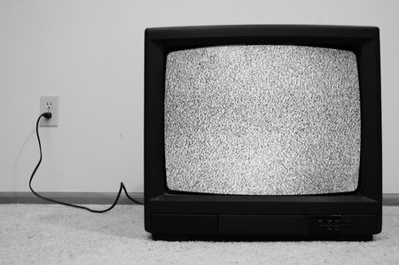 retro tv: An old CRT TV plugged into the wall with static on the screen. Stock Photo
