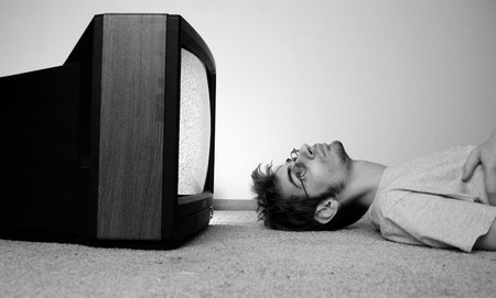 mesmerized: An old CRT TV plugged into the wall with static on the screen with a man watching it closely.