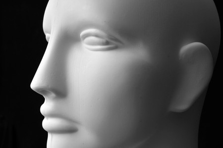 Front view of a mannequin dummy head isolated on a black background.