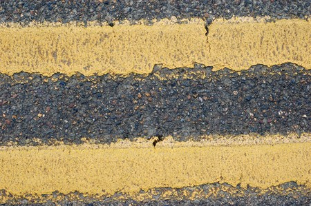 Cracks in a double yellow lined road. Makes a good texture photo
