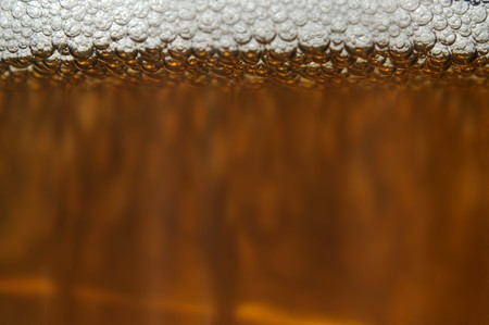 A closeup of dark beer in a cup with bubble suds at the top Stock Photo - 7850393