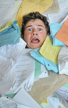 overwhelm: Young male student is overwhelmed by way too many homework assignments.