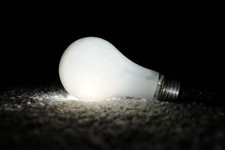 Unscrewed illuminated light bulb on the floor, brightly lit in the darkness. Black background copyspace above.