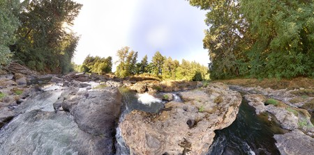 equirectangular: An earhtly rocky river with trees and sky with an extreme wide angle Stock Photo