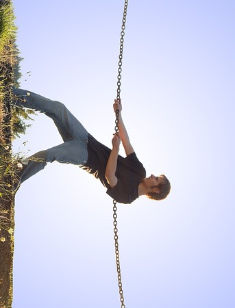 Young man trying to climb up a wall grabbing onto a chain