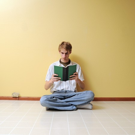 A young male reading a small hardcover book in an empty room with lots of copyspace around his body. photo