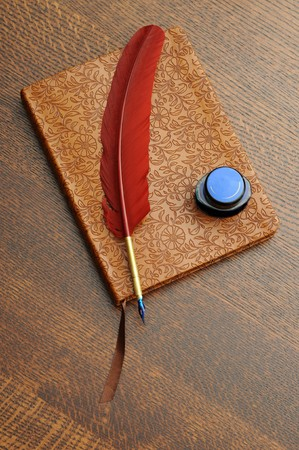 A closed journal with a feather pen and ink ona  wooden table.