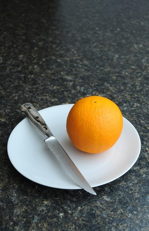 An orange fruit on a white plate with a knife photo