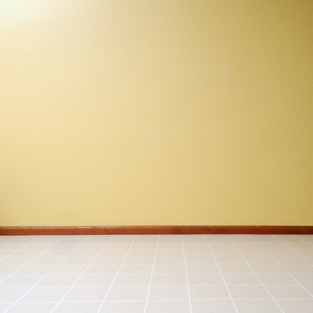 Empty room with a linoleum floor with a yellow painted wall photo