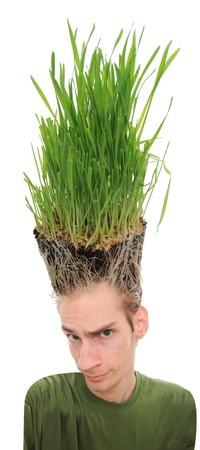 coupe de cheveux homme: Un jeune homme regardant vers le haut � l'herbe qui pousse des racines au-dessus de sa t�te. Ce concept peut s'appliquer � des environnementalistes, des agriculteurs, l'agriculture, paysagistes, jardiniers, et les coupes de cheveux fous.