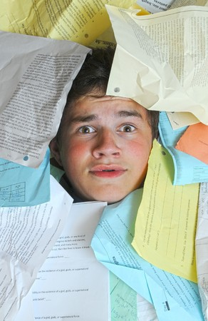 assignments: Young male student is overwhelmed by way too many homework assignments.