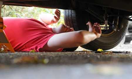 underneath: A white Caucasian male mechanic works on an old automobile car.