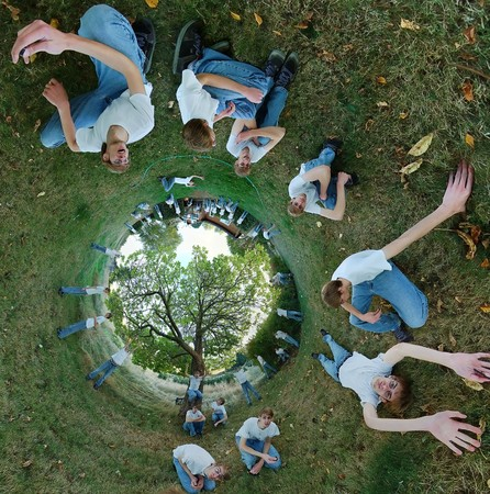 multiplicity: A 360x180 stereographic panorama with a young teenage man laying down on the grass in several different positions, with a tree inside of a circle.