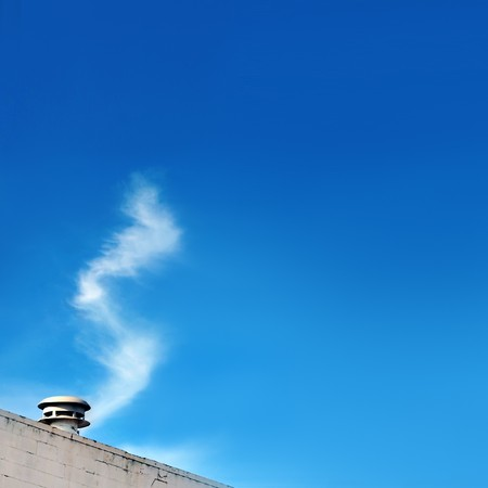 forced perspective: Clouds appear to be coming out of the steaming vent. In trick photography, this technique is known as forced perspective. Blank emptyy blue sky copyspace with room for your text. Stock Photo