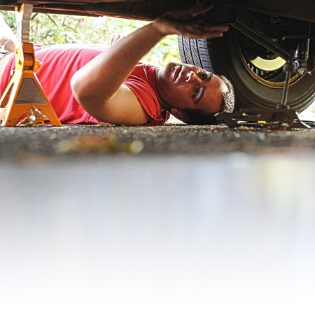 A white Caucasian male mechanic works on an old automobile car. photo