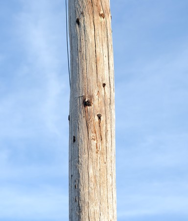 telephone pole: A wooden telephone pole log with a blue sky background. Stock Photo