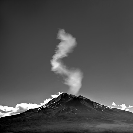Mount Shasta with smoke or steam or clouds coming up through the top of the mountain.  photo