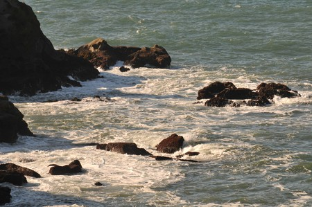 Sea rocks with waves crashing against them. Above viewpoint. photo