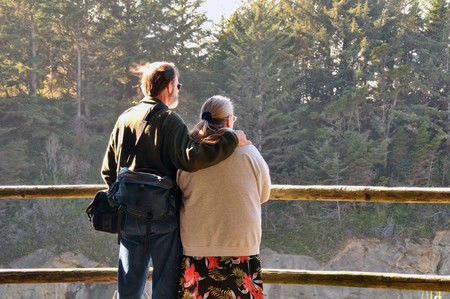 Tourist heterosexual couple enjoying a nice peaceful afternoon above a wilderness viewpoint. photo