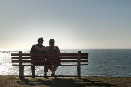 banc de parc: Silhouette d'un couple h�t�rosexuel profiter l'apr�s-midi sur un calme et paisible de d�tente en face de la vue sur l'oc�an. Copyspace ci-dessus avec place pour le texte. Banque d'images