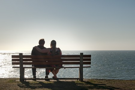 retired: Silhouette of a heterosexual couple enjoying the afternoon on a calm and peaceful relaxing in front of the ocean view. Copyspace above with room for text. Stock Photo