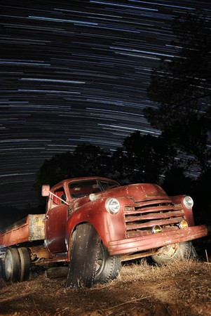 An old red truck in a field at night time with star trails above. photo