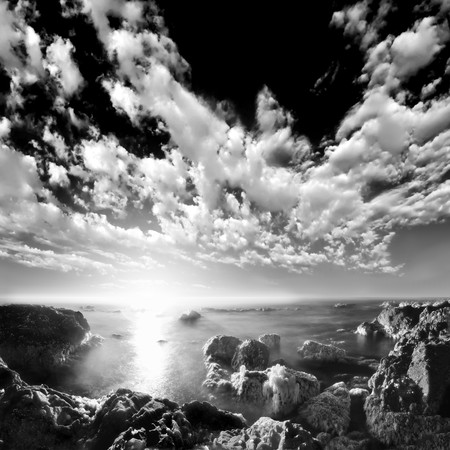 A long exposure of ocean water between sea rocks at the beach with beautiful clouds above the horizon. Black and white infrared photograph 스톡 콘텐츠
