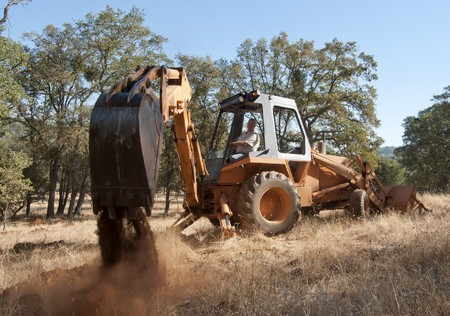 A backhoe digging up some dirt holes in the ground. photo