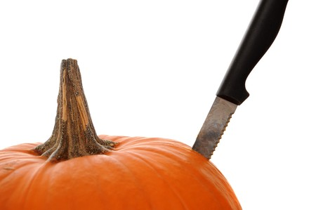 stabbing: Orange pumpkin  isolated on a white background with a knife stabbed in the side to demonstrate a pumpkin carving theme.