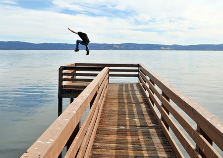 outstretched: A man jumping a long narrow wooden pier into the calm blue ocean water with outstretched victorious arms.