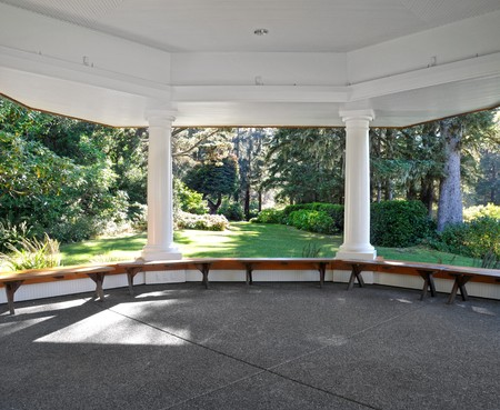 A large gazebo with study pillars supporting it on a cement pad. Inside interior shot. photo