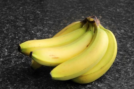 kitchen counter top: Bananas on a black kitchen counter top. Stock Photo