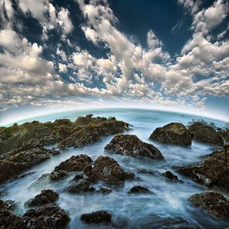A long exposure of blue water between rocky sea ocean shore at the beach with beautiful clouds above the horizon.