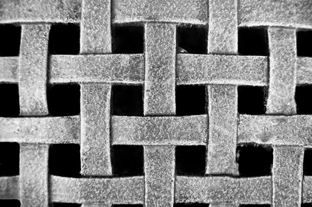 Woven Metal Mesh Grid Pattern on a black background photo