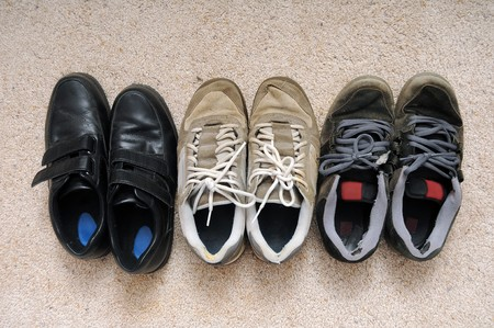 Three pairs of old shoes. One formal, the other two skateboarding shoes. photo