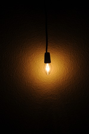 A small clear light bulb hanging next to a wall
